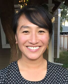 A headshot of a smiling Vietnamese-American woman in her thirties.  She is wearing gold dangly earrings, and a black and white patterned shirt.  Her hair is pulled back into a bun and she has long bangs swept to the left side.  She is outside and there is a tree behind her.