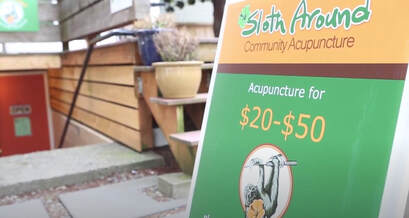 An orange and green A-Frame sign reads Sloth Around Community Acupuncture.  Off to the side, the entrance to the clinic is visible.  The clinic entrance has concrete steps and a black handrail on the right hand side.