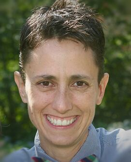 A headshot of a white woman in her late forties smiling.  She has a short haircut, and brown eyes.  She is outside and there are green leaves behind her.  She is wearing a blue checkered button up shirt and a multicolored bow tie.
