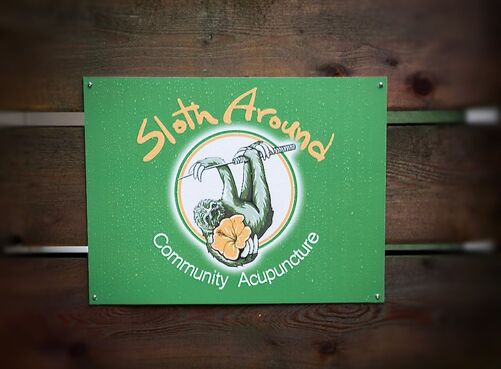 A green sign reads Sloth Around Community Acupuncture.  In the center of the sign is a drawing of a three toed sloth hanging from an acupuncture needle.  The sloth holds an orange hibiscus flower in its right hand.  The sign has rain drops on it, and is nailed to three horizontal wooden boards.