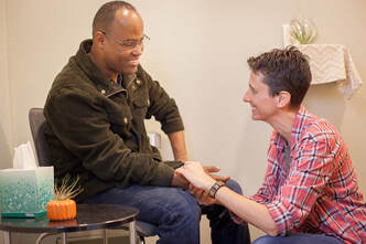 A Black man sits in a chair wearing jeans and a black jacket.  He is smiling.  Sloth Around acupuncturist Lynn kneels on the ground to take his pulse on his right hand.  She is wearing a red flannel button up shirt and smiling.